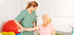 nurse and elderly woman doing physical therapy