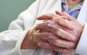 senior holding hands together